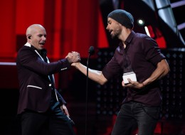 Enrique Iglesias, right, presents Pitbull with the Latin AMA Dick Clark achievement award at the Latin American Music Awards at the Dolby Theatre on Thursday, Oct. 26, 2017, in Los Angeles. (Photo by Chris Pizzello/Invision/AP)